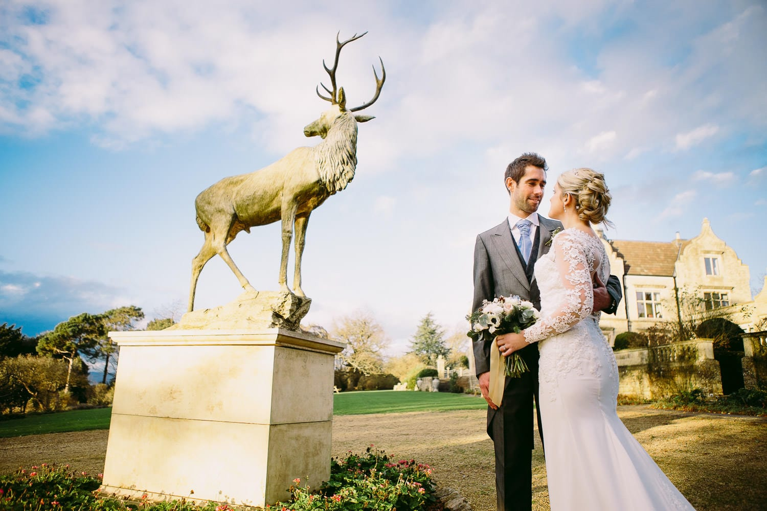 A bride and groom in front of Old Down Manor