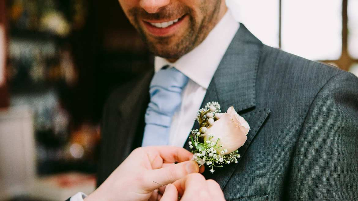 A groom has his corsage fixed