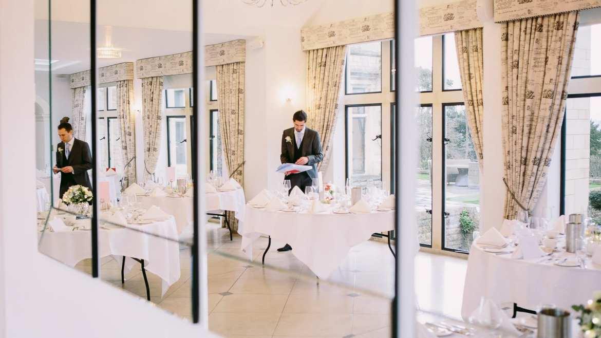 A groom setting up the tables