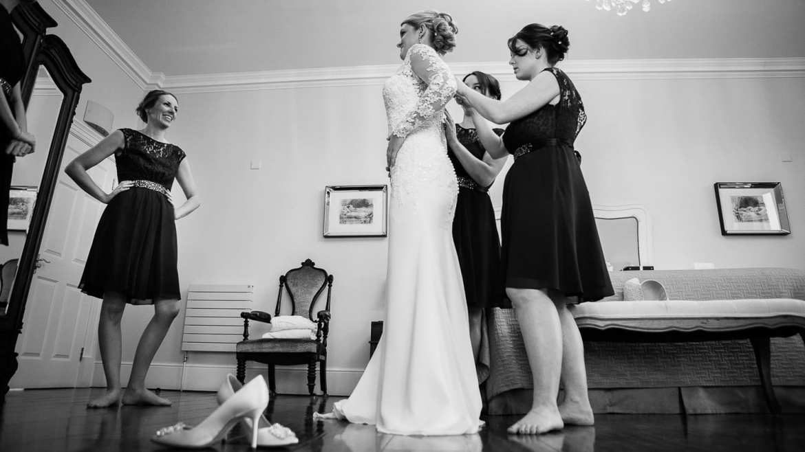 Bridesmaids help a bride put her dress on