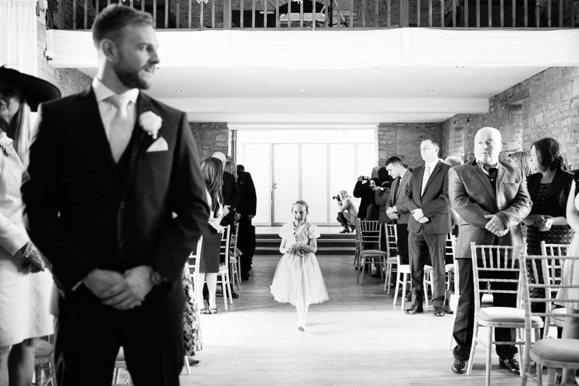 The groom waits as one of the flower girls comes down the aisle