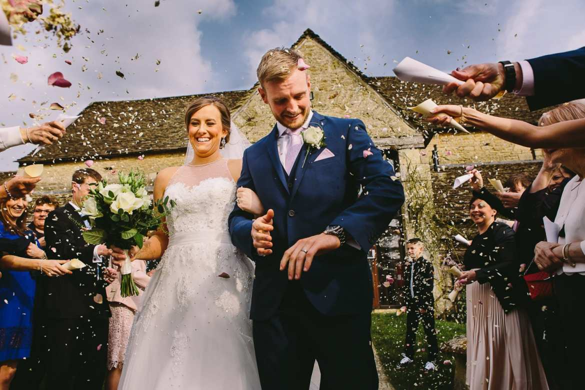 The bride and groom get showered with confetti outside the great tythe barn