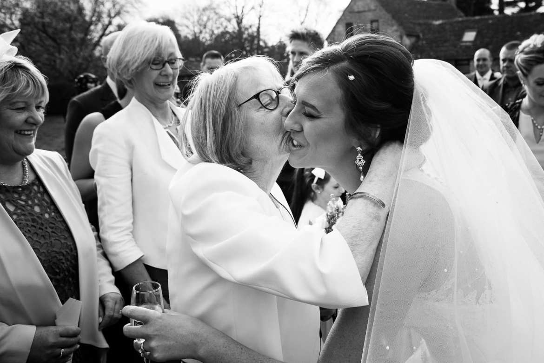 Grandma kisses and congratulates the bride after the ceremony