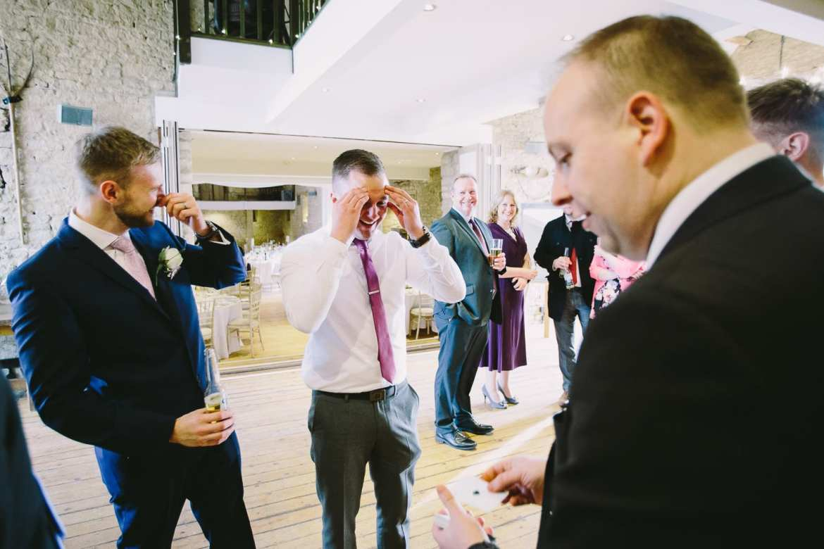 A guest and the groom look amazed as they watch a card trick