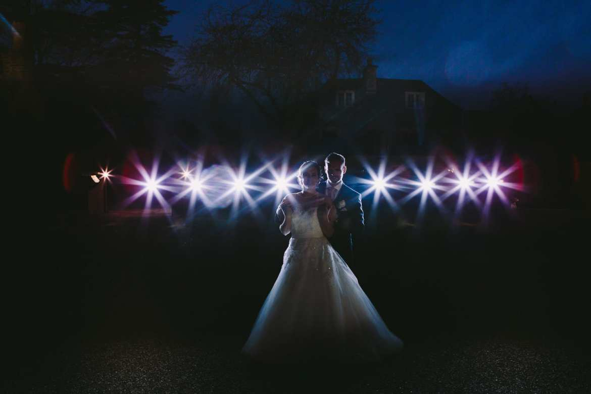 A night time portrait of the bride and groom with flashes behind them