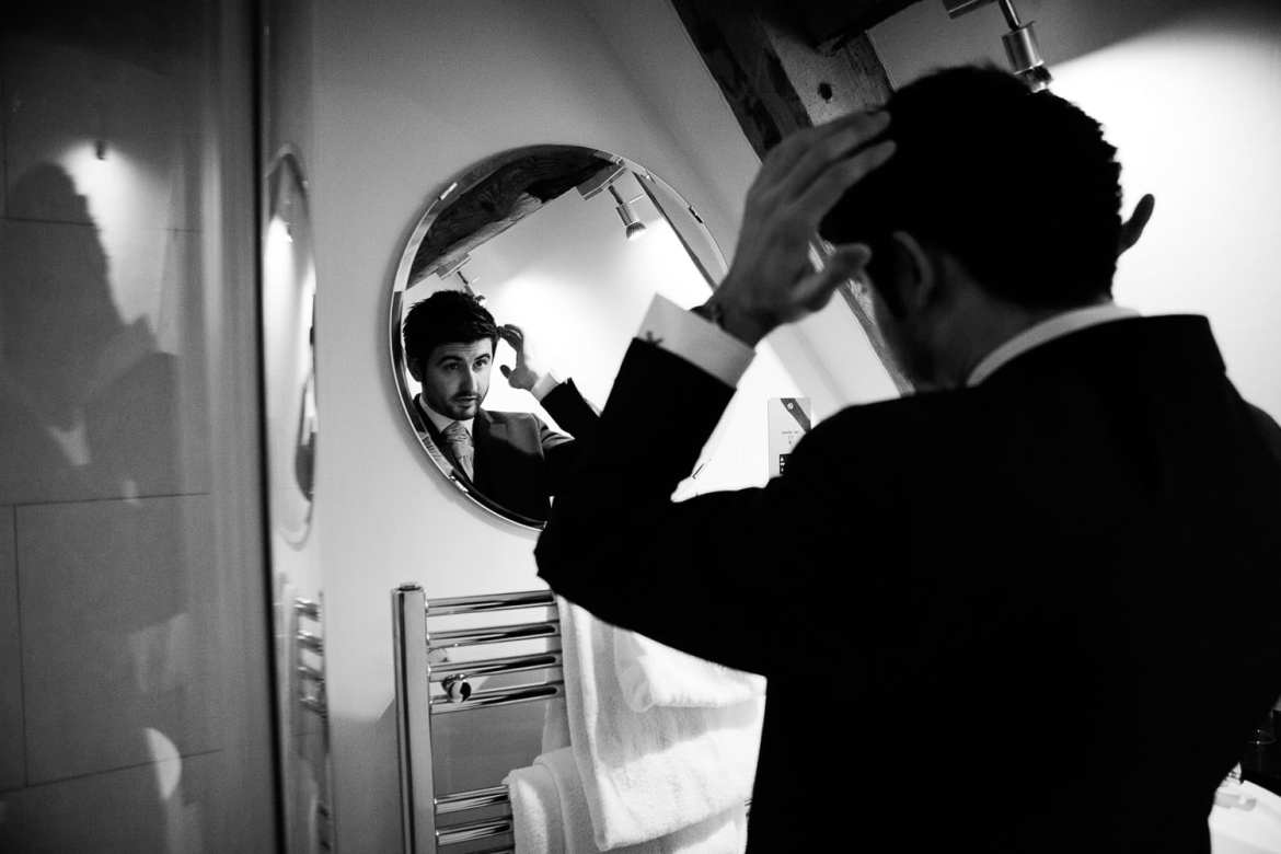 The groom sorts his hair out in front of a mirror
