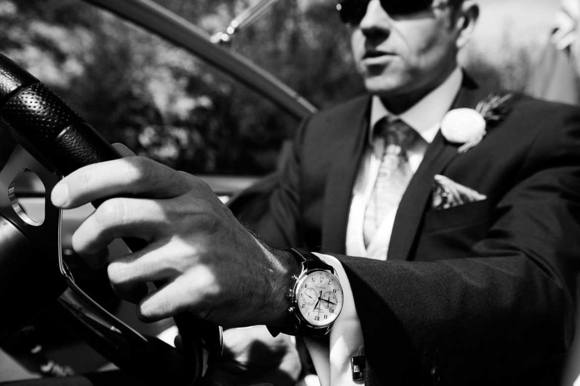 The groom driving the boat and showing off his new watch