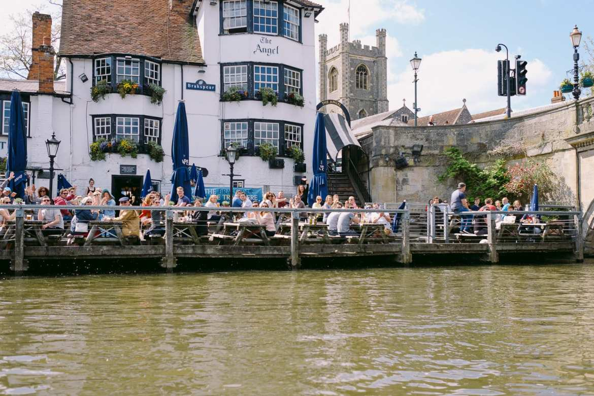 Wellwishers waving from the banks of the Thames in Henley