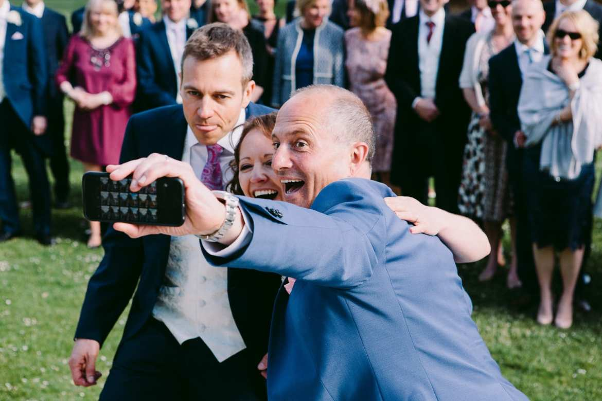 Bride and groom having a selfie with their celebrant at Greenlands