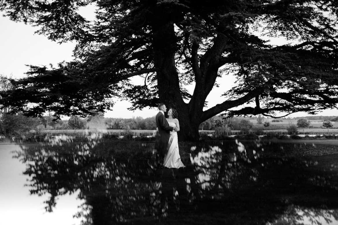 Black and white relfection portrait of bride and groom in gardens at Greenlands