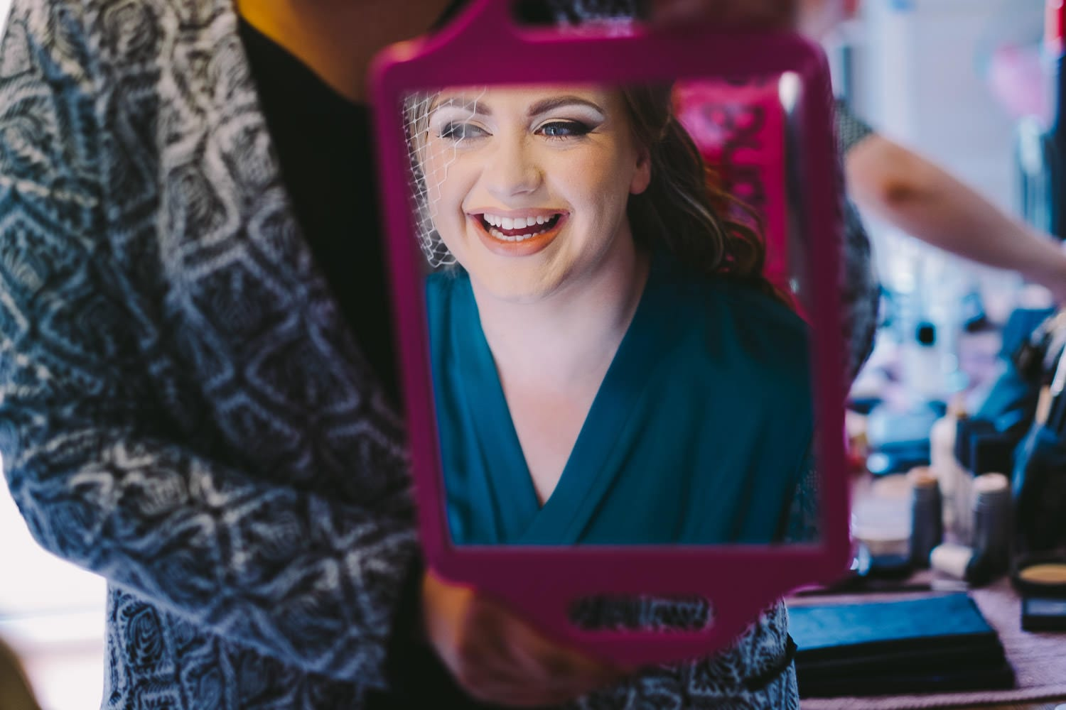 Laughing bride reflected in a mirror