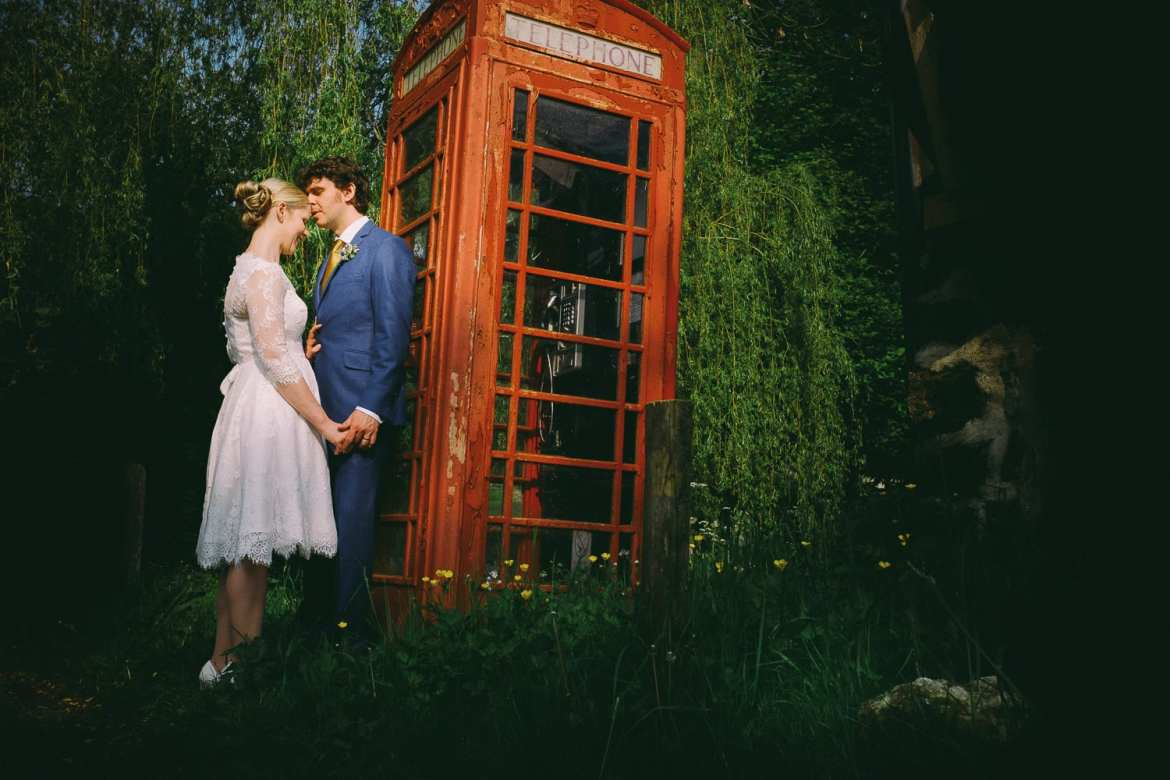 The bride and groom outside a phonebox