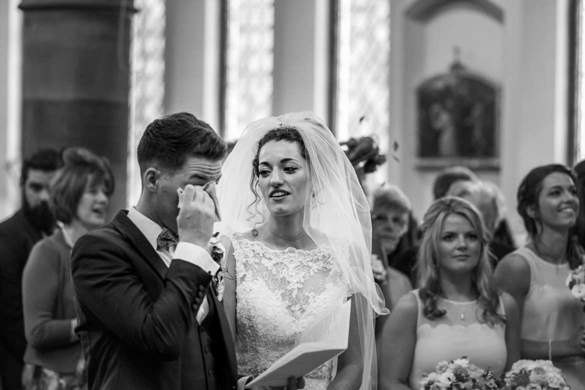 The groom wipes away a tear in the church