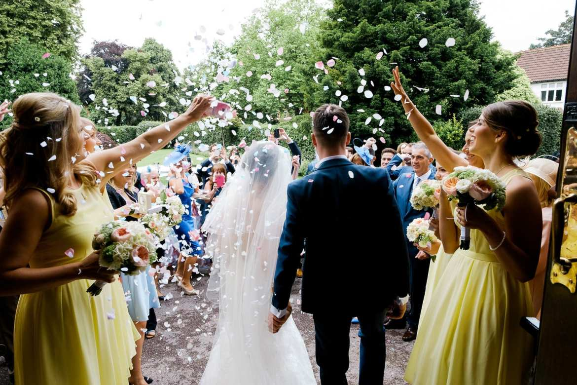 The bride and groom from behind with confetti