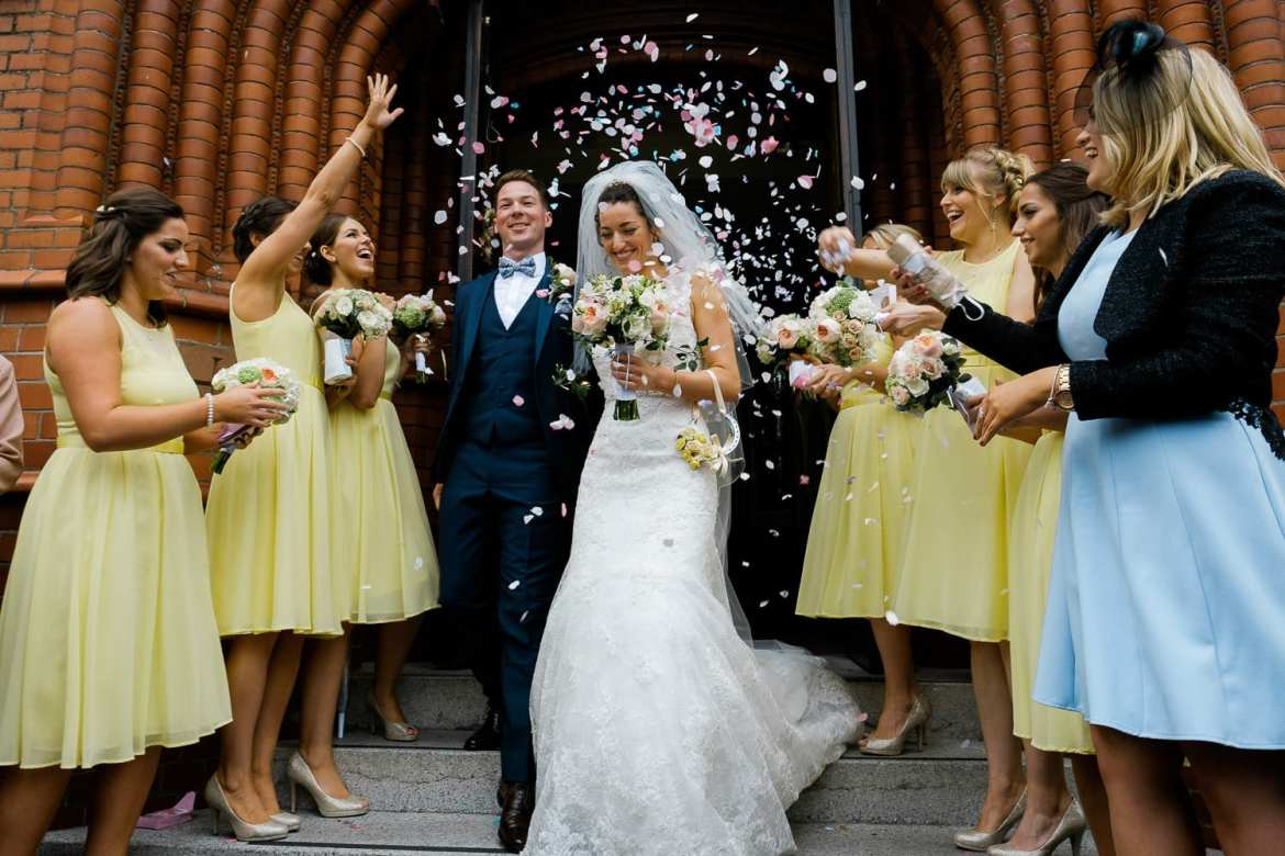 Confetti is thrown over the bride and groom