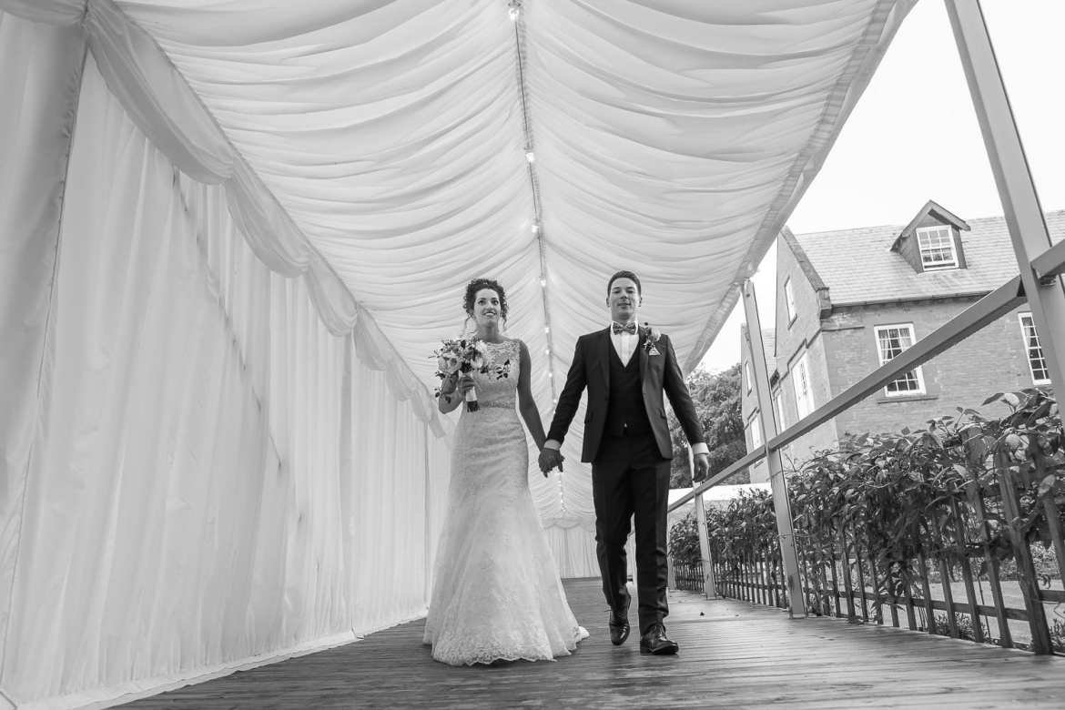 The couple walking to the marquee at Nunsmere hall