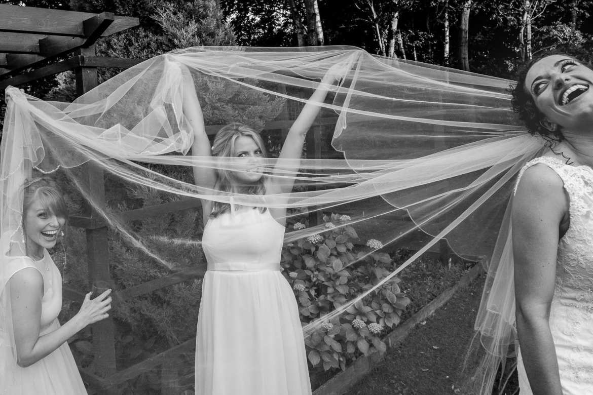 The bridesmaids being silly with the bride's veil