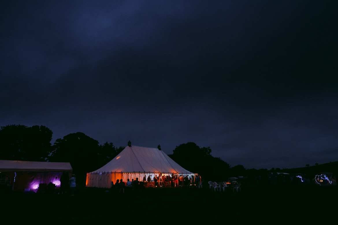 The festival wedding tent lit up at night