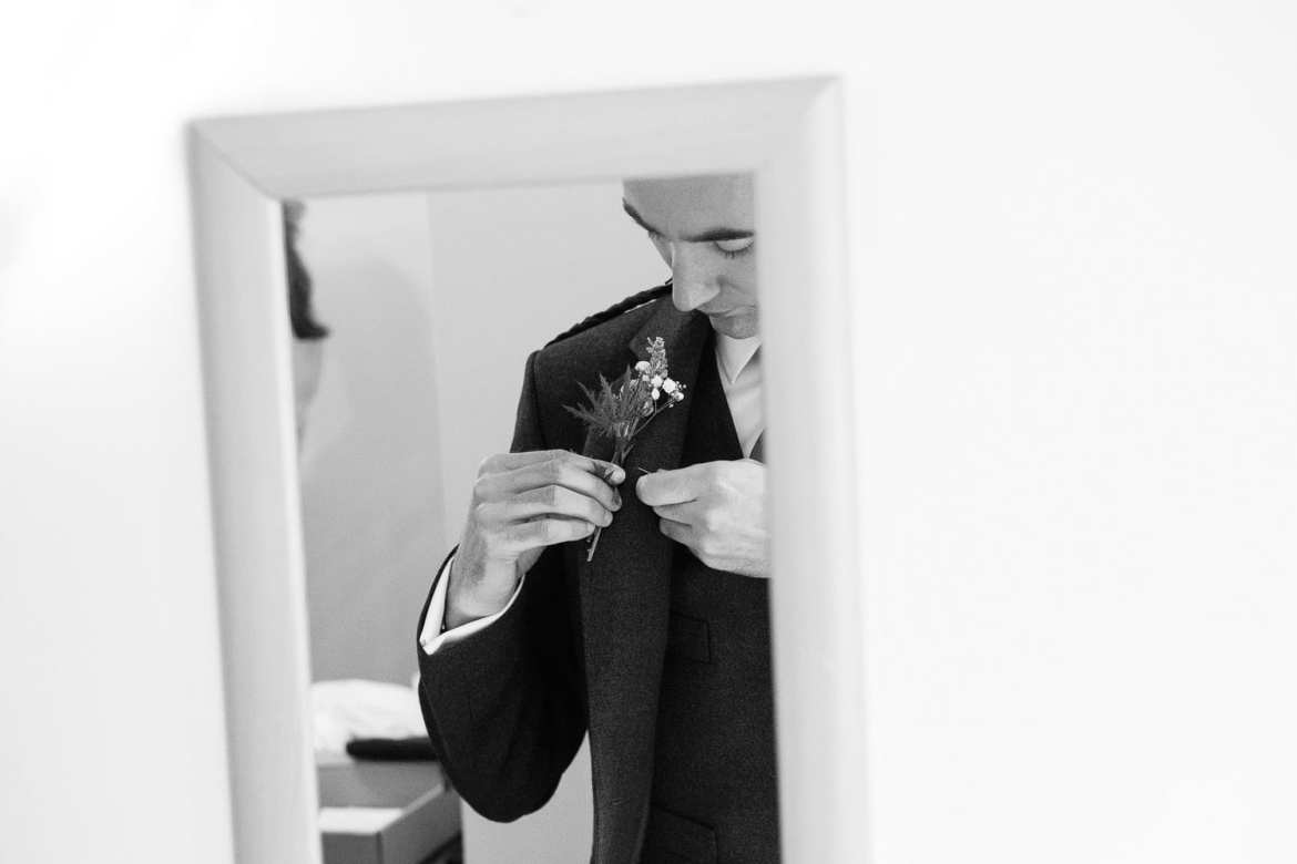 Groom in the mirror adjusting his corsage