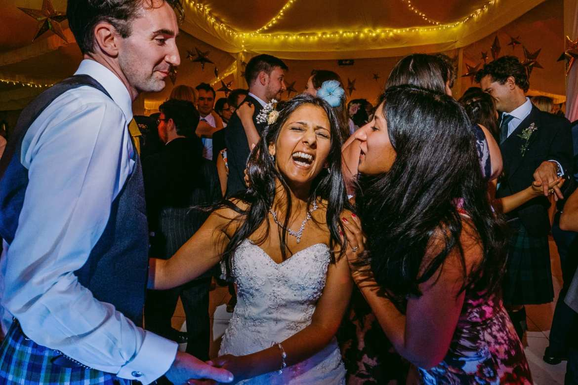 The bride laughing on the dance floor with her sister