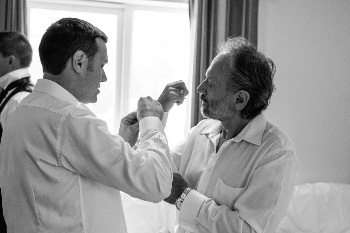 The groom helps his dad with cufflinks