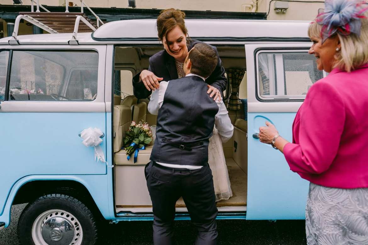 The groom lifts the bride from the camper van