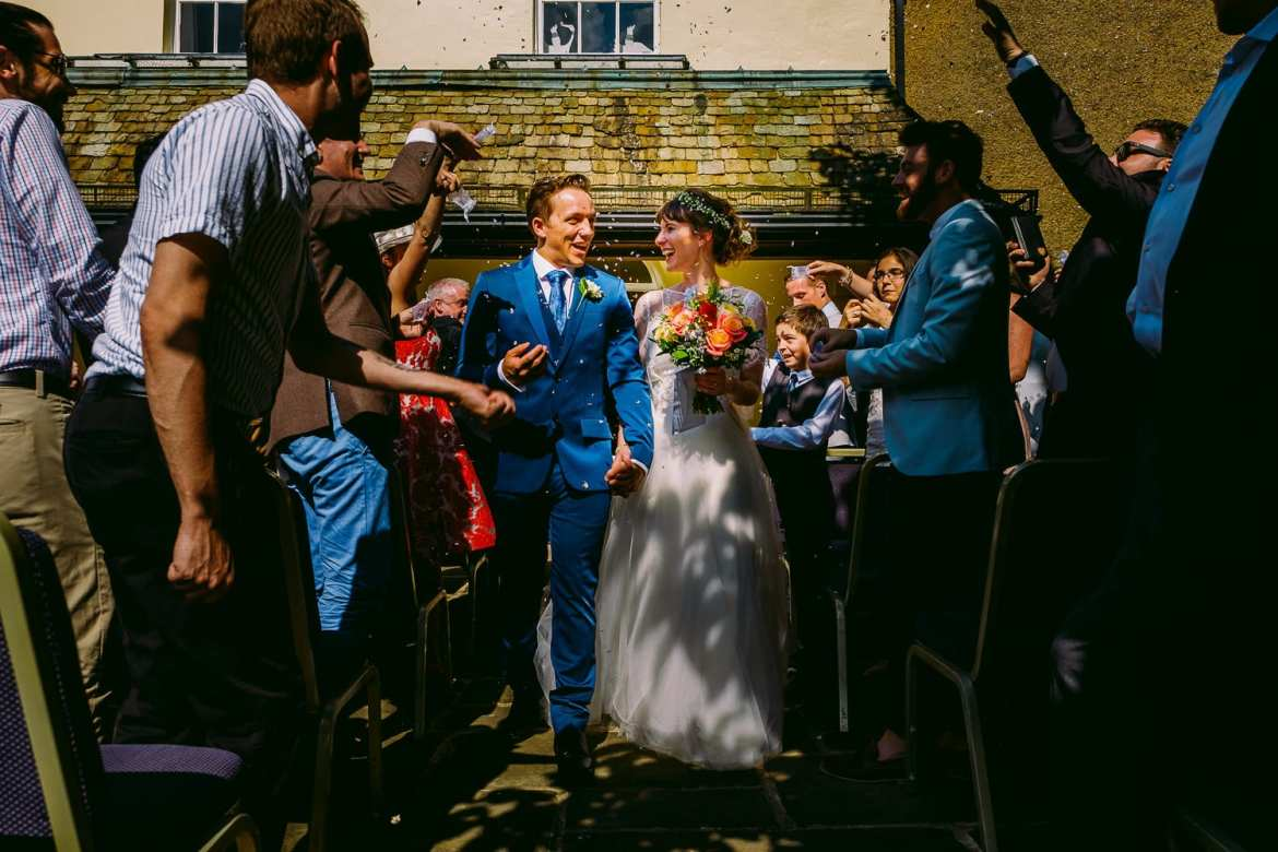 The wedding guests throw confetti over the newlyweds