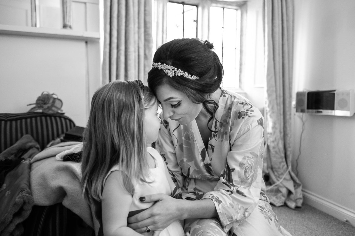 The bride and a flower girl share an intimate moment before the wedding