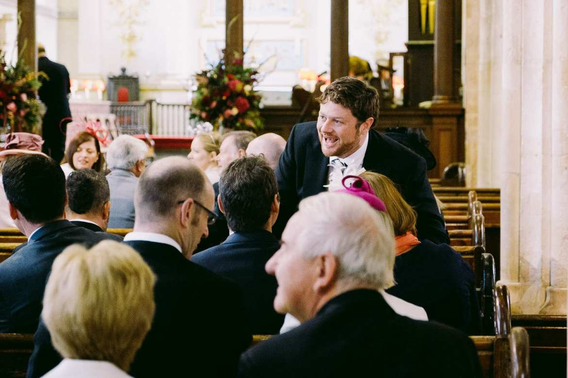 The groom shares a joke with some wedding guests