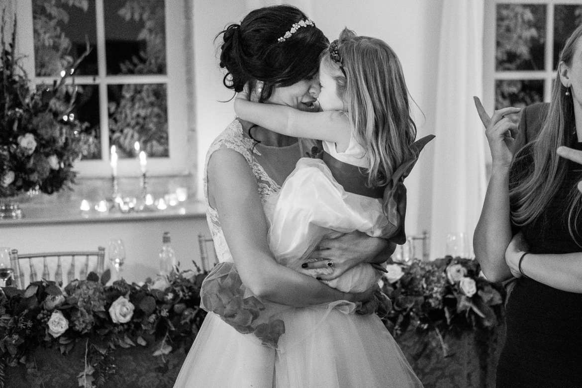 The bride hugs a flower girl