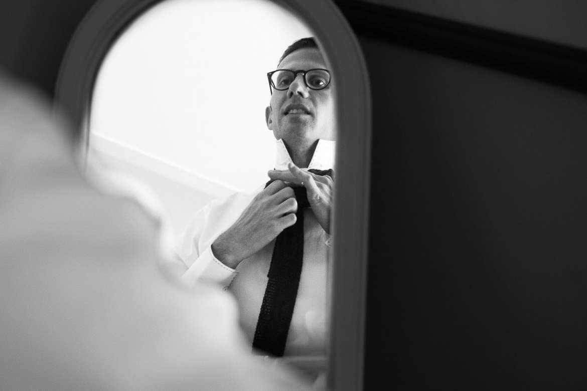 Groom adjusting his tie in the mirror