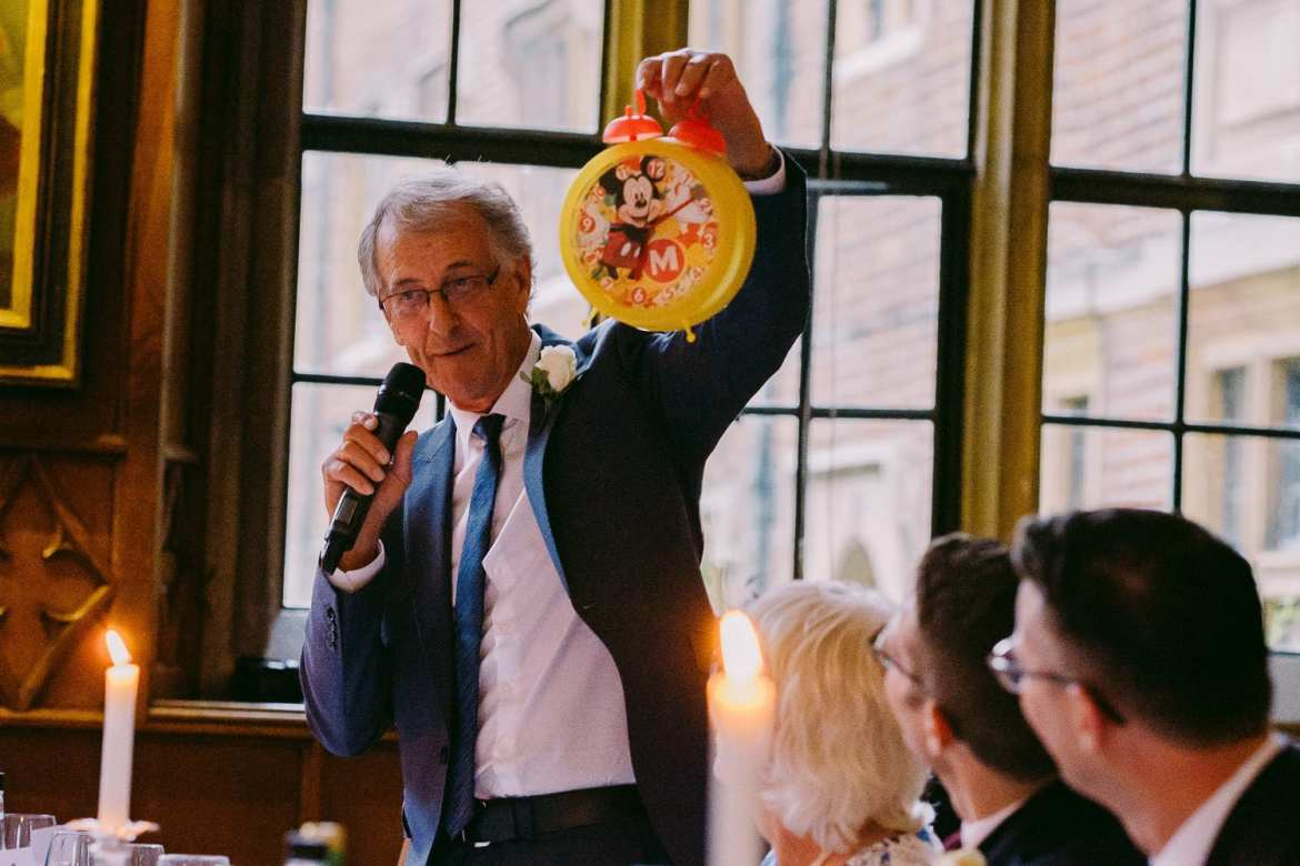The ather of the groom holds up a Mickey Mouse clock