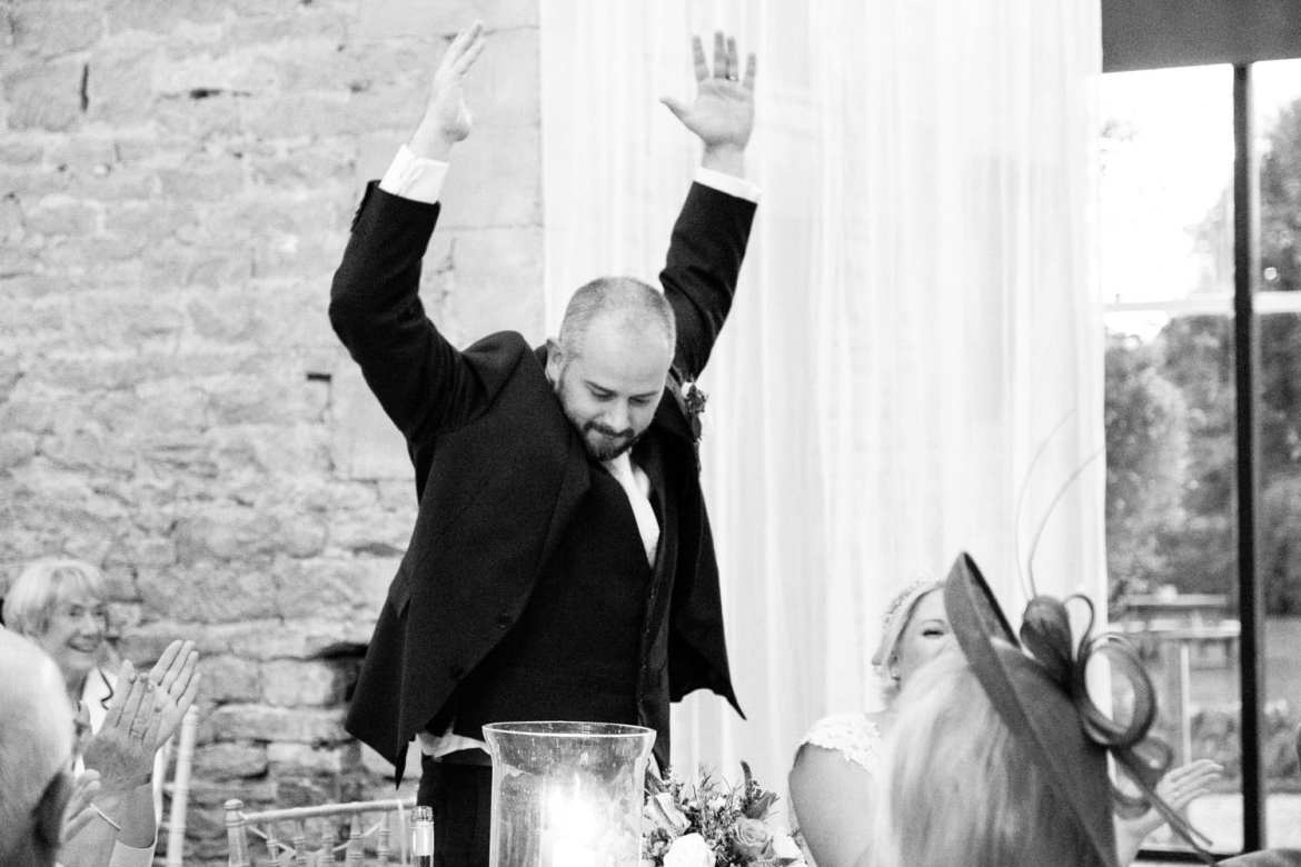 Groom throws his arms in the air during the speeches