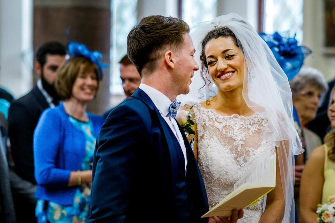 Bride and Groom smiling at each other in church