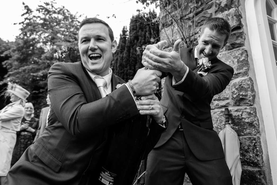 The groom and best man struggling to open a magnum of champagne