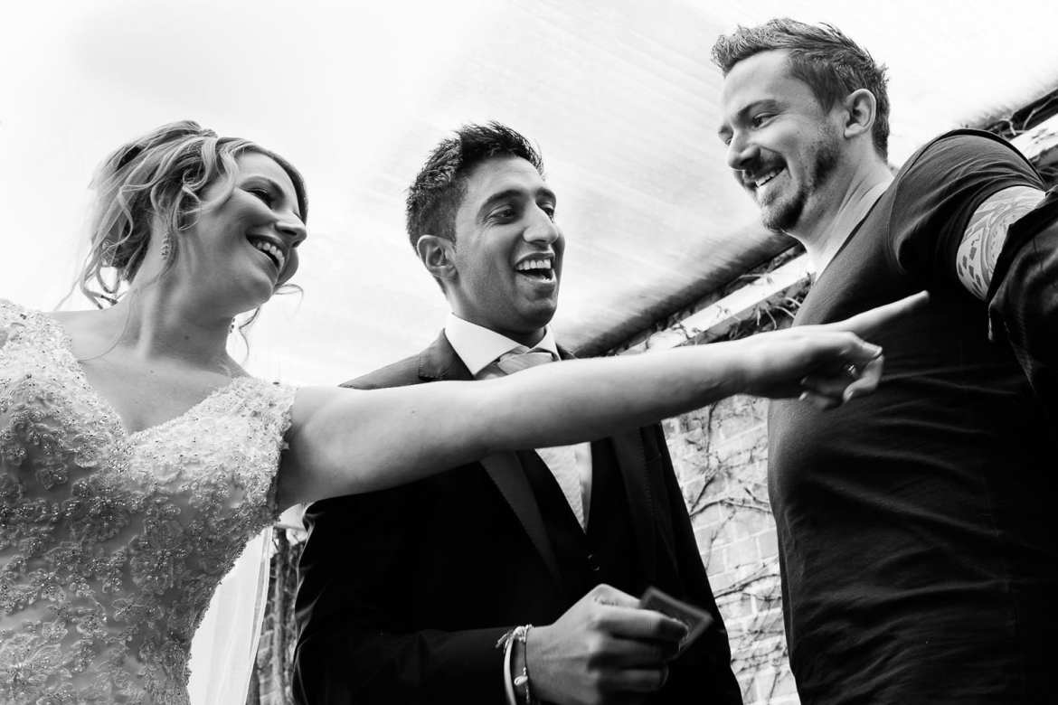 A magician reveals the card tattooed on his arm while the bride and groom look amazed and laugh
