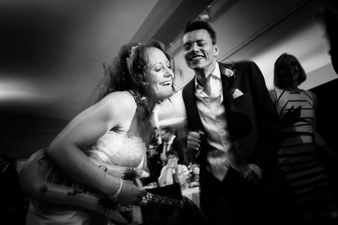 The bride and best man dancing. The bride is playing an inflatable guitar