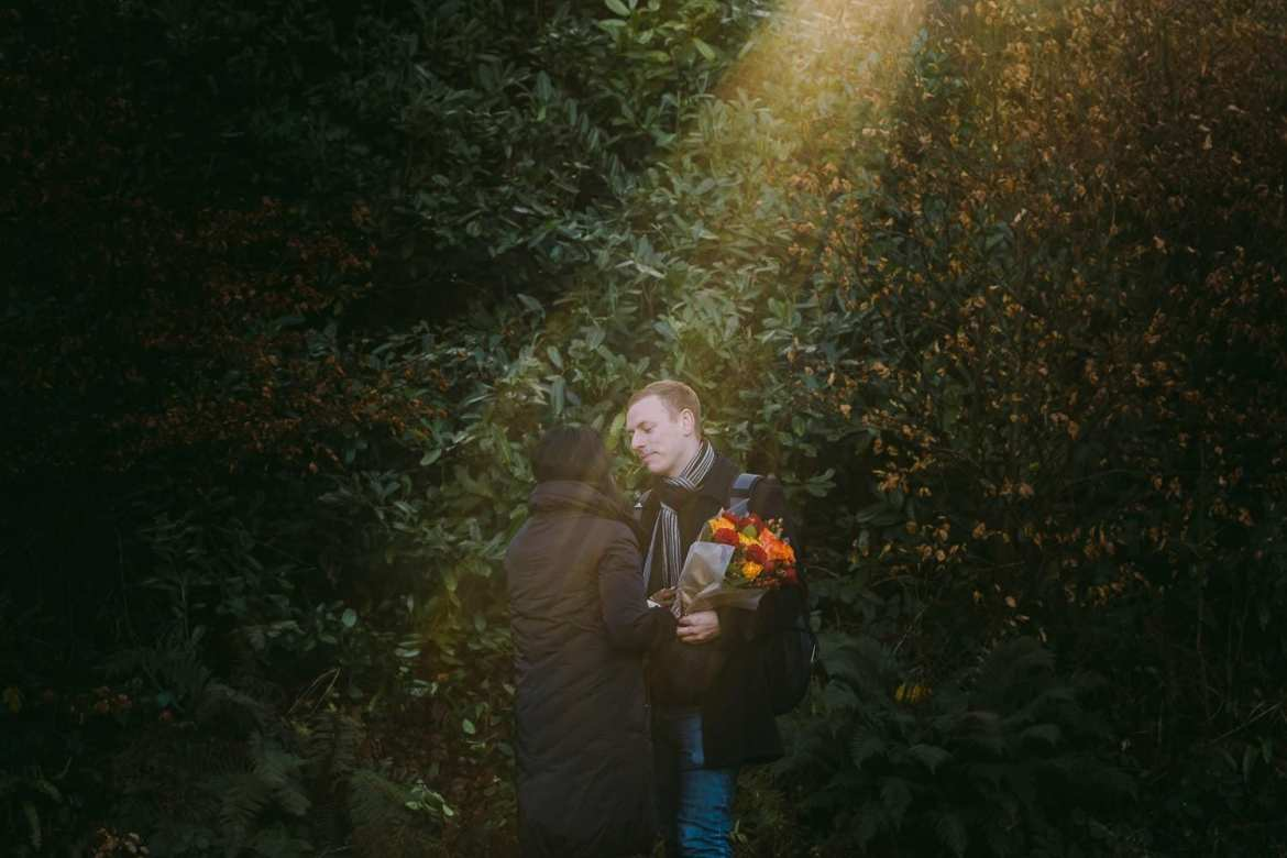 The newly engaged couple in a beam of light