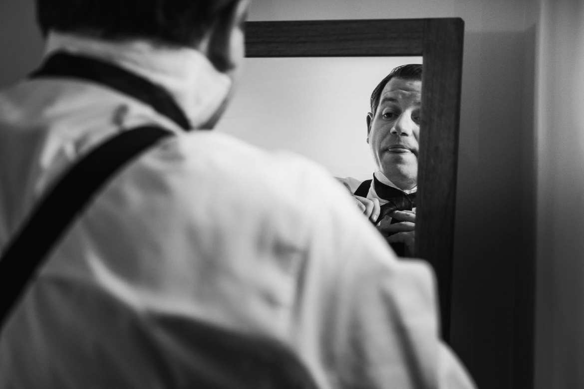 The groom tiers his tie in the mirror