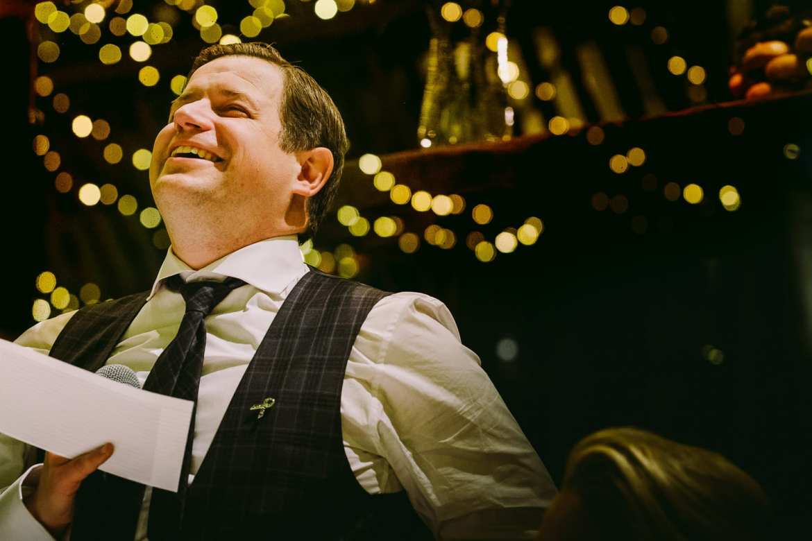The groom laughing during his speech