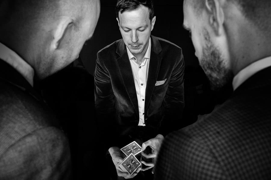 A magician does a card trick as two bald headed men look on