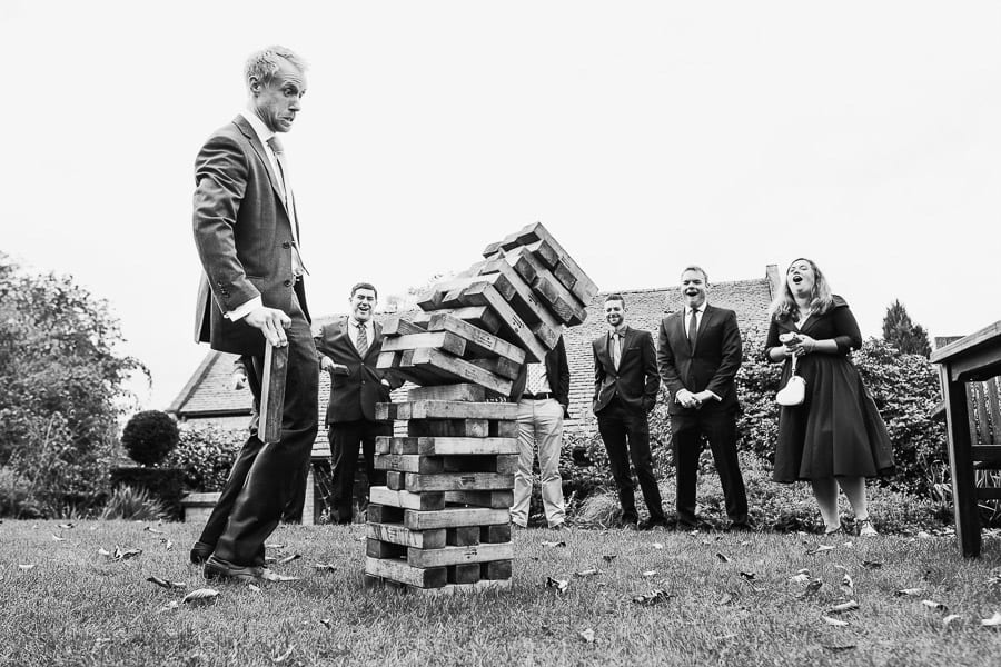 A wedding guest looks startled as the jenga falls