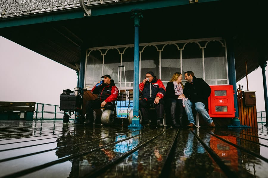A couple looking at each other sat next to some fishermen at Clevedon Pier