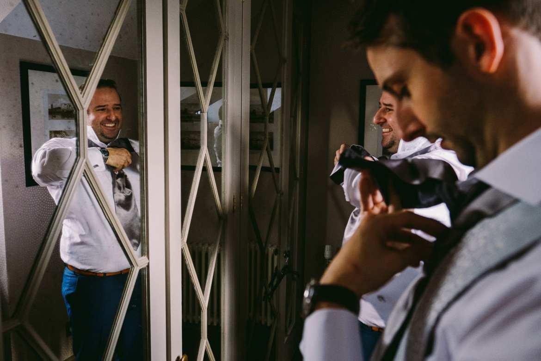 Groom doing his tie in the mirror