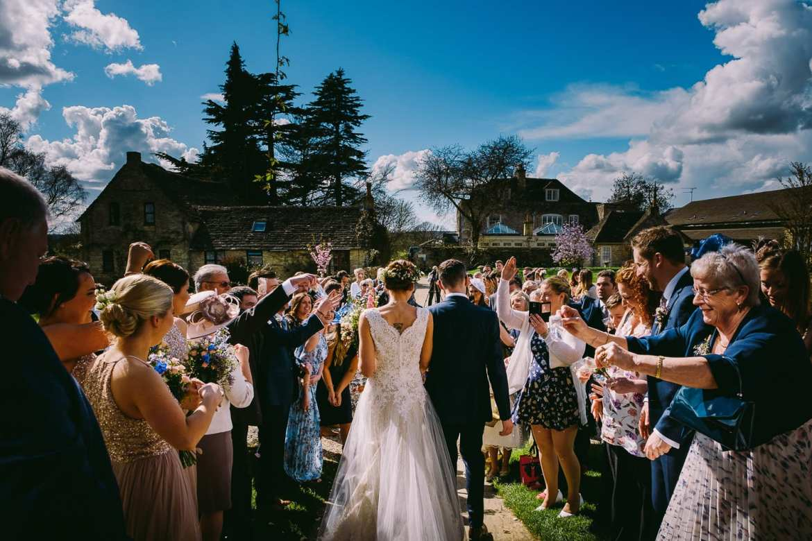 Zia & Ady walk out to meet their guests at the Great Tythe Barn in Tetbury