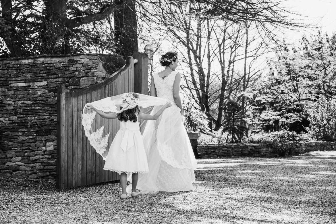 A flower girl lifts the bride's veil over her head