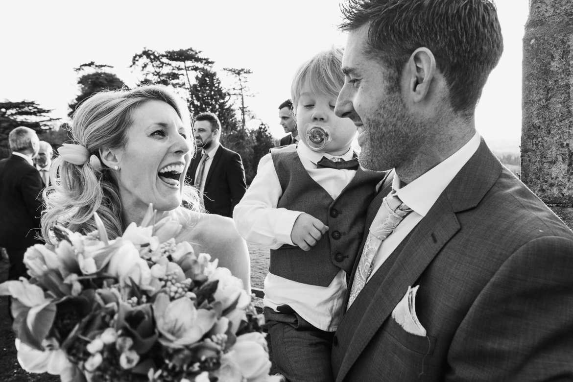 A bridesmaid laughs with the groom