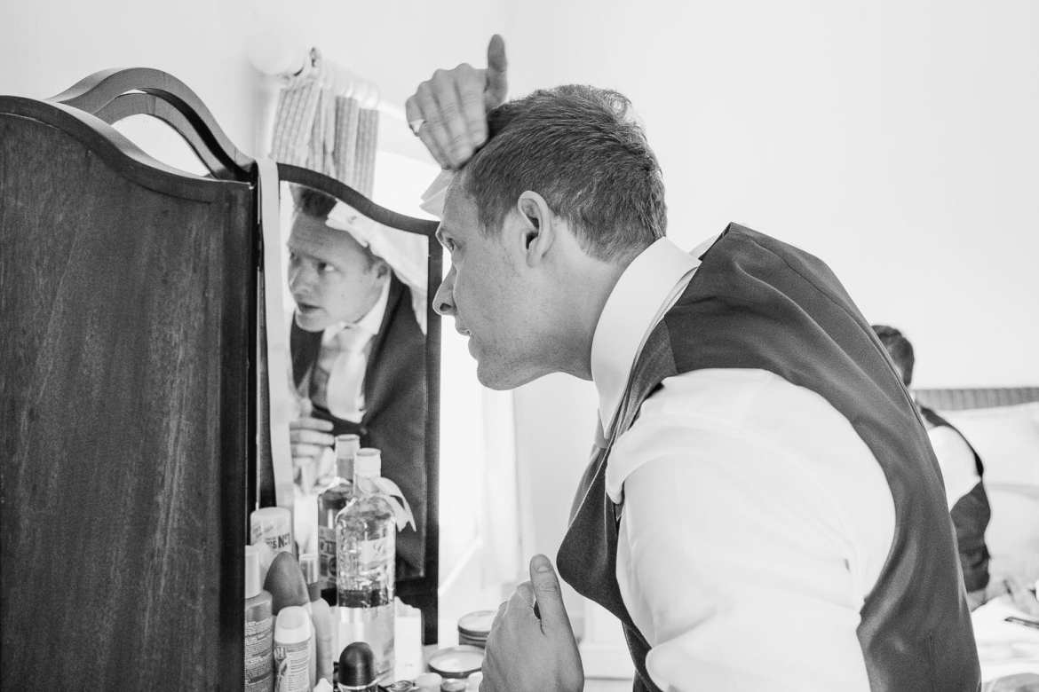 The groom getting ready in the mirror