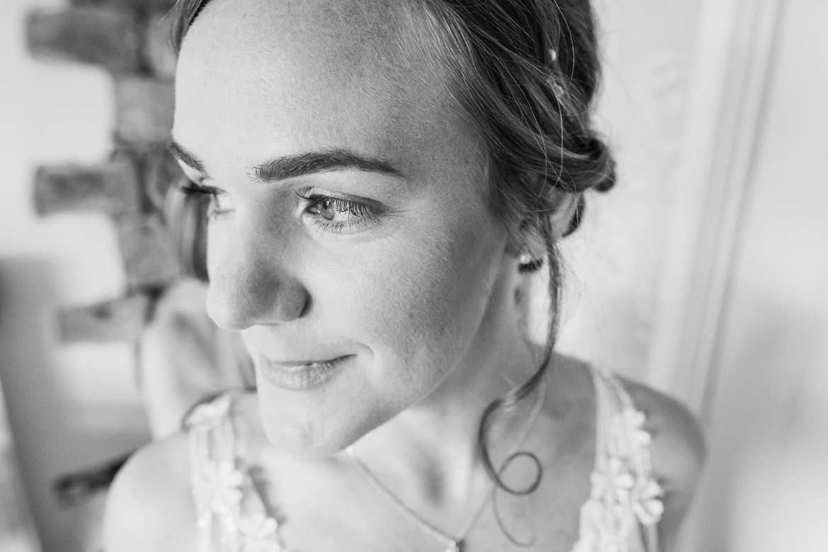 A black and white portrait of the bride in her dress getting ready