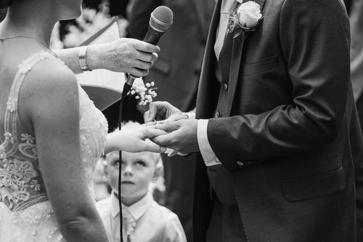 A young ring bearer looks on as the couple exchange rings